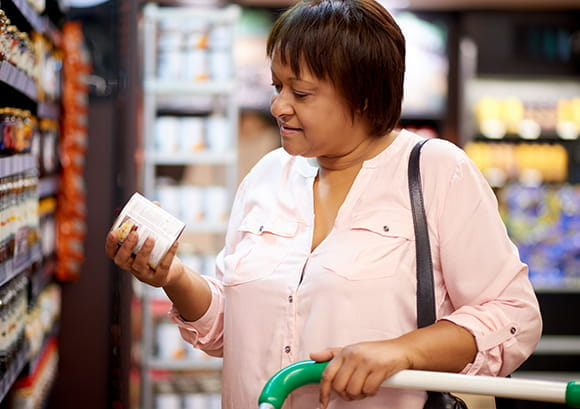 Woman Reviewing Canned Good Health Ingredients in Supermarket