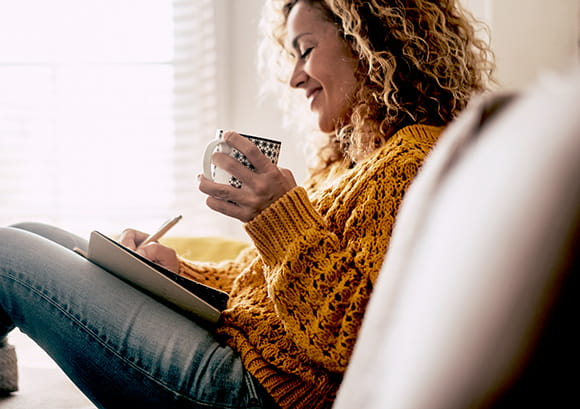 Woman writing in a journal and drinking a cup of tea