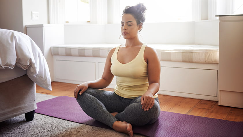 Young woman sitting on a yoga mat and meditating