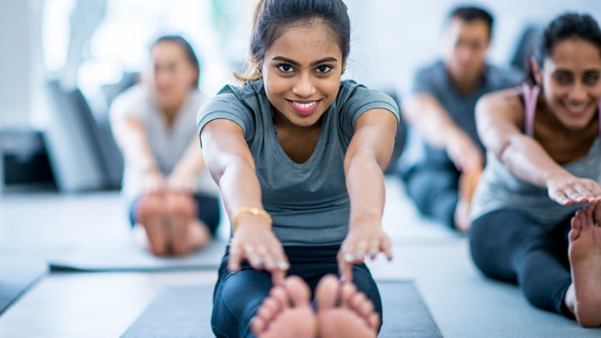 Seated young woman stretching in a group fitness class