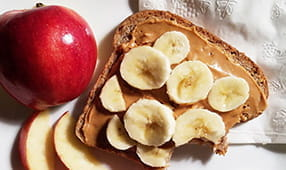 Peanut butter and banana on whole wheat bread alongside apple slices