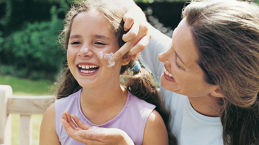 Mother applying sunscreen to her daughter's cheek