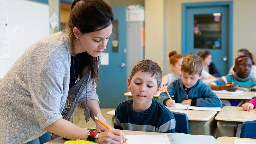 How to Cope With 7 Common Educator Health Problems - Female Teacher Helping a Young Student at His Desk