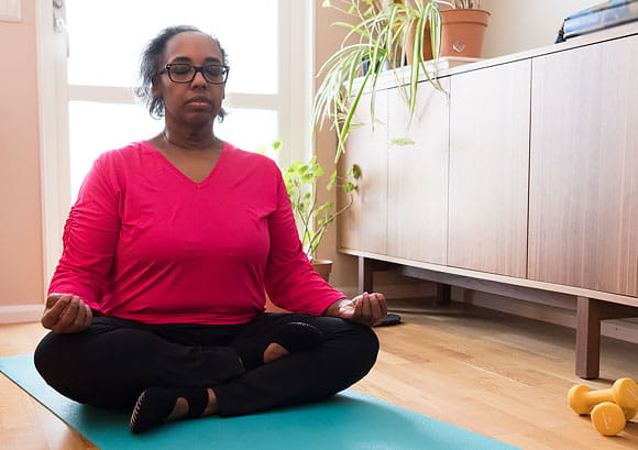 Older African-American Woman Exercising Indoors and Doing Yoga