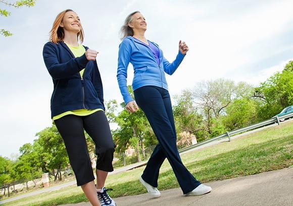 Two women briskly walking in a park