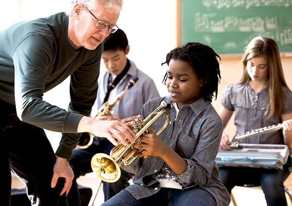 Older male teacher instructing young music students