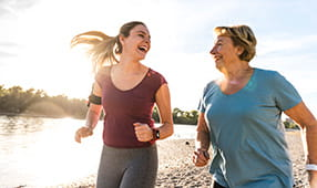 Mother and daughter having fun, jogging together along a river