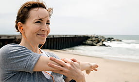Smiling woman listening to music and stretching her arm while on the beach