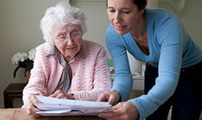 Elderly Woman Being Assisted with Paperwork