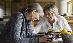 Senior Women Laughing and Drinking Coffee at Dining Table