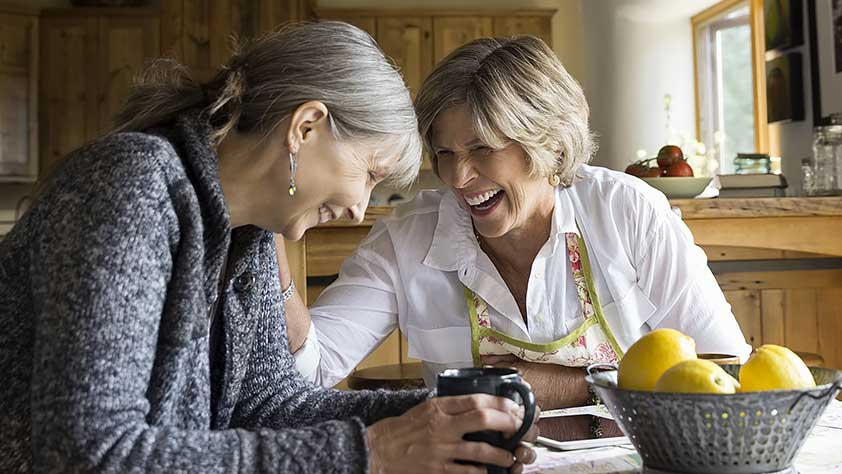 The Importance of Life Insurance Over Age 50 - Senior Women Laughing and Drinking Coffee at Dining Table