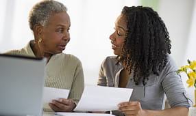 Young woman explaining finances to elder
