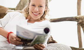 Smiling woman reading a magazine