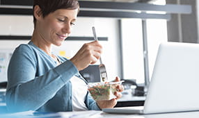 Woman eating lunch in front of her laptop