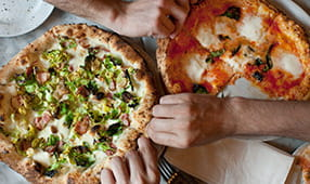 Close-up of hands reaching for two kinds of healthy pizza