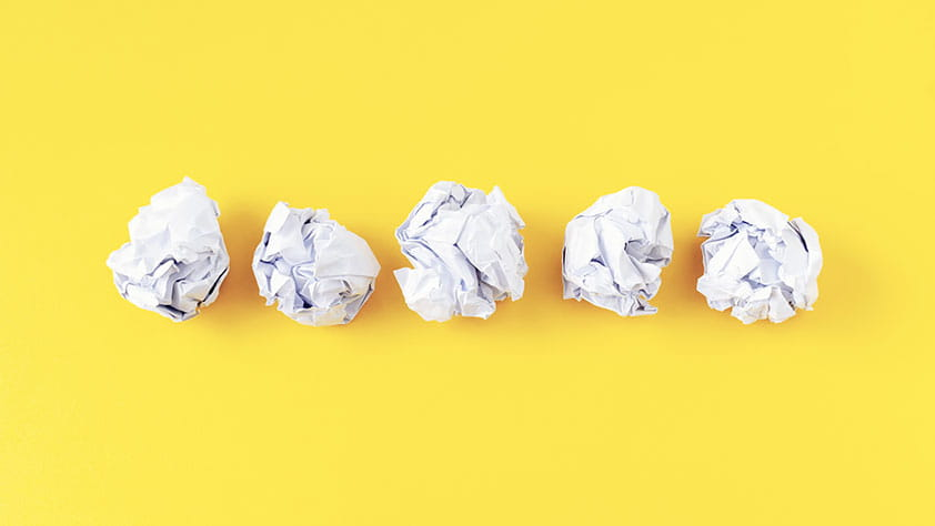 5 Money Mistakes Educators Need to Avoid - photo of five crumpled sheets of paper on yellow background