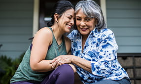 Senior Woman and Adult Daughter Hugging and Laughing on Porch