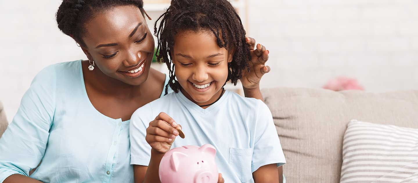 Mother and Young Daughter Putting Coins Into Piggy Bank