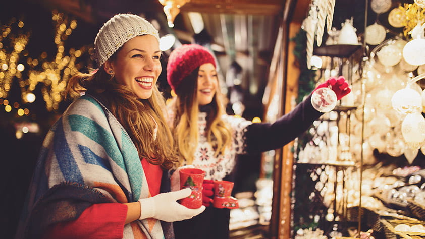 Two young women shopping at a holiday market