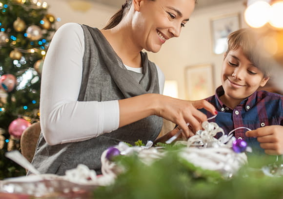 Mother and Son Opening Gifts in Front of Christmas Tree