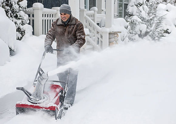 Man Clearing Driveway with a Red Snowblower
