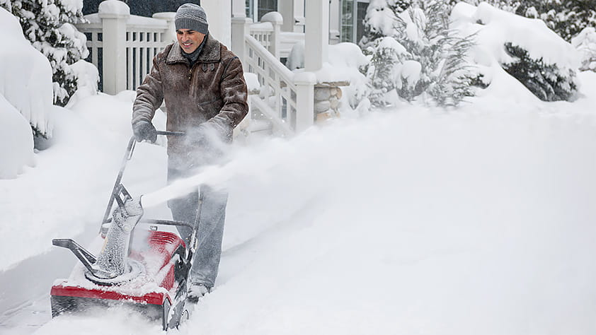 Why You Might Need Extra Cash This Winter - Man Clearing Driveway with a Red Snowblower