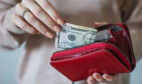Fifty Dollar Bill Being Placed in Wallet