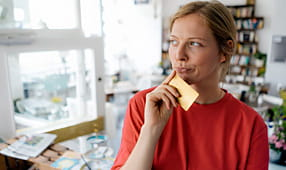 Woman Holding a Credit Card and Thinking