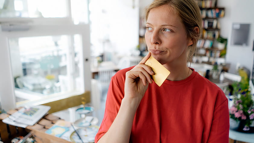 Credit Card Myths - Woman Holding a Credit Card and Thinking