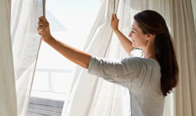 Woman Smiling Opening Curtains in Bedroom