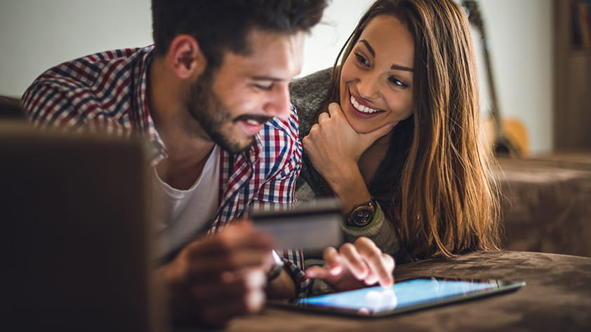 Couple Happily Making Purchase on iPad