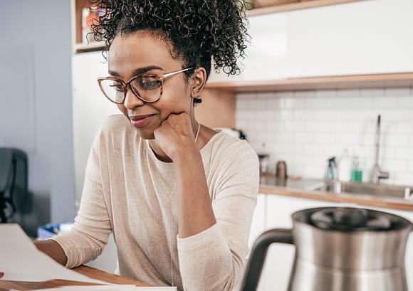 African-American Woman Wearing Glasses Reading Paperwork