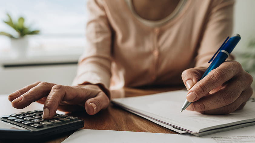 Woman sitting at a table using a calculator and writing on a notepad
