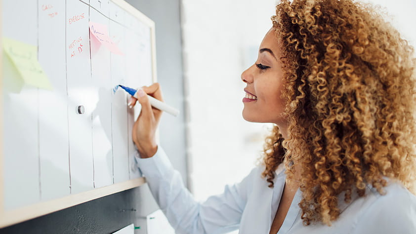 Woman writing notes on her wall calendar