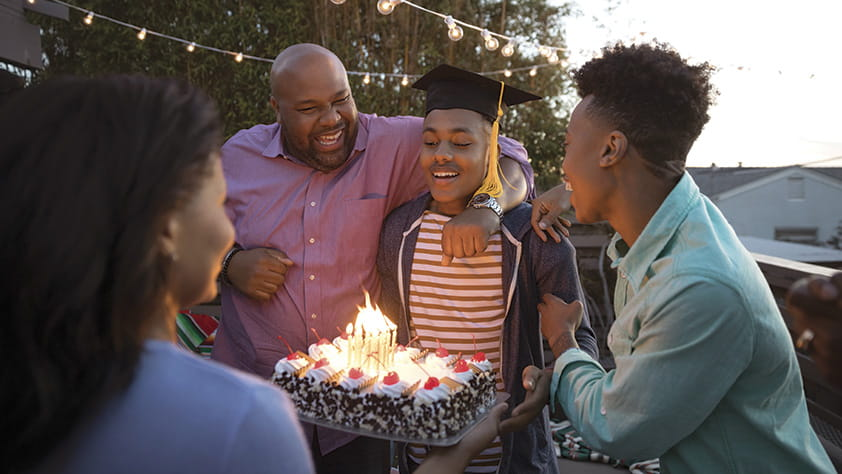 Family celebrating their son's graduation with cake on their backyard deck