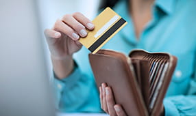 Female Hands Close Up of Credit Card Being Placed into Wallet