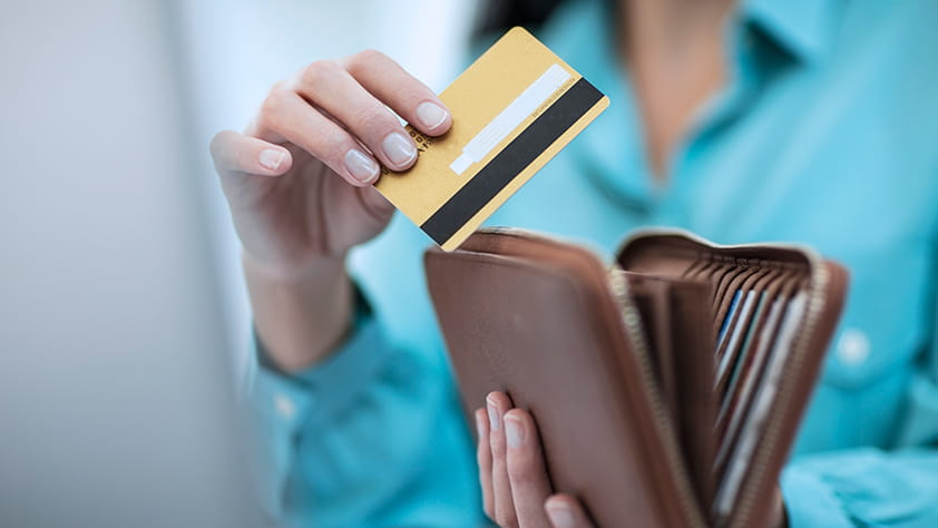 Close-up of a woman in a turquoise shirt taking a credit card out of her wallet