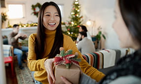 Young woman handing a holiday present to a friend