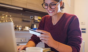 Young woman holding a credit card and shopping from home on her laptop