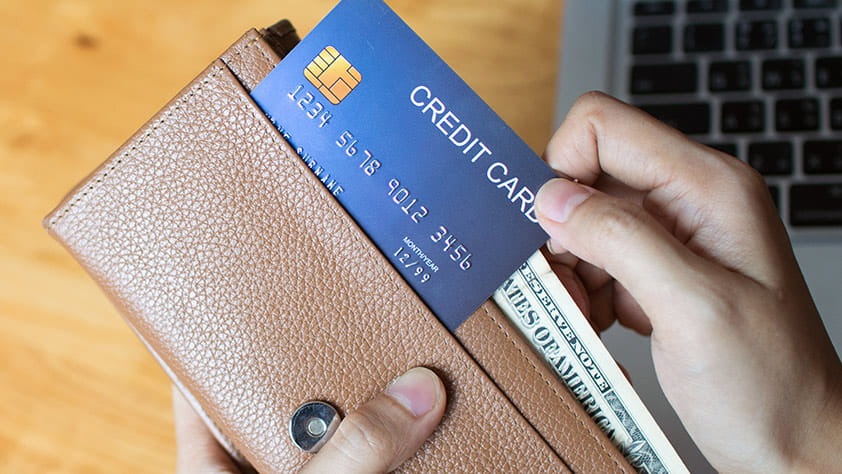 Close Up of Credit Card Being Placed into Wallet