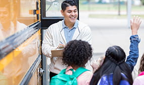 Bus Driver Taking Role of Students Outside of Bus Entrance