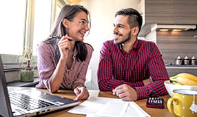 Husband and Wife Smiling While Reviewing Financial Information
