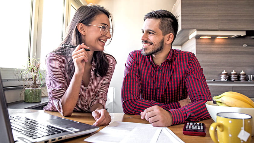 Couple sitting at their kitchen table using a laptop and looking at paperwork