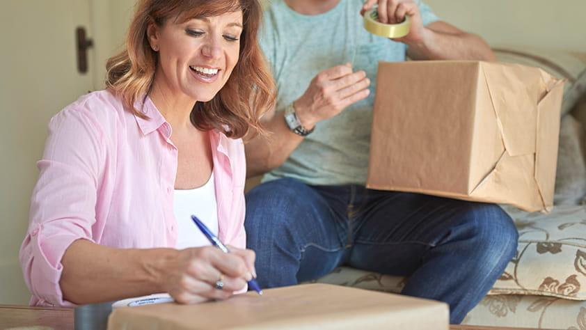 Woman writing an address on a shipping box