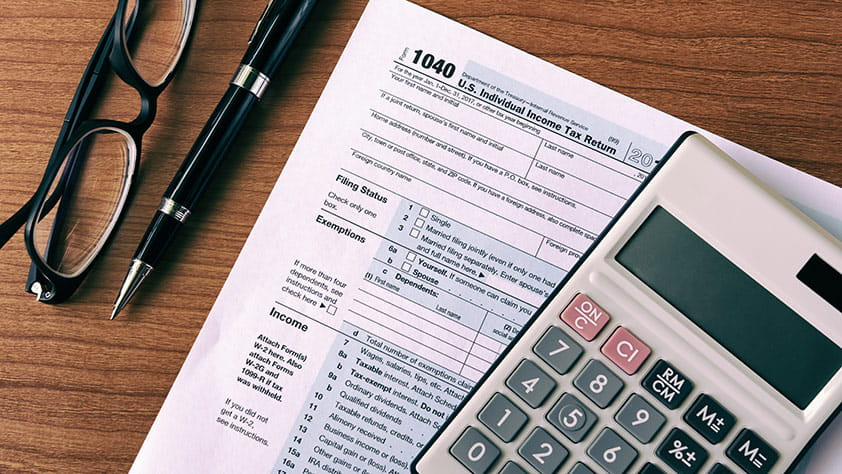 Calculator, a pair of glasses, a pen and tax forms on a wooden table
