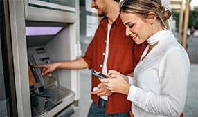 Woman smiling while banking online using her mobile phone as a young man happily uses an ATM