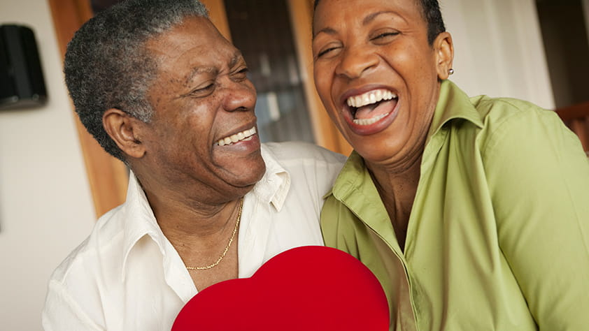 Happy African-American older couple holding a bright red heart-shaped box of chocolates