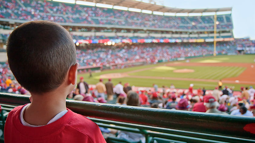 Young boy at a baseball game looking out onto the baseball field