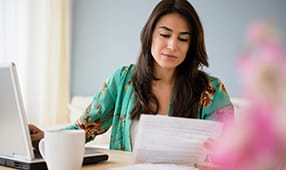 Young Woman Doing Finances on Laptop