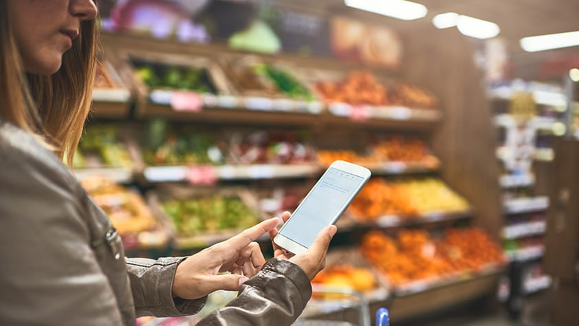Woman Staring at Cell Phone in Produce Aisle